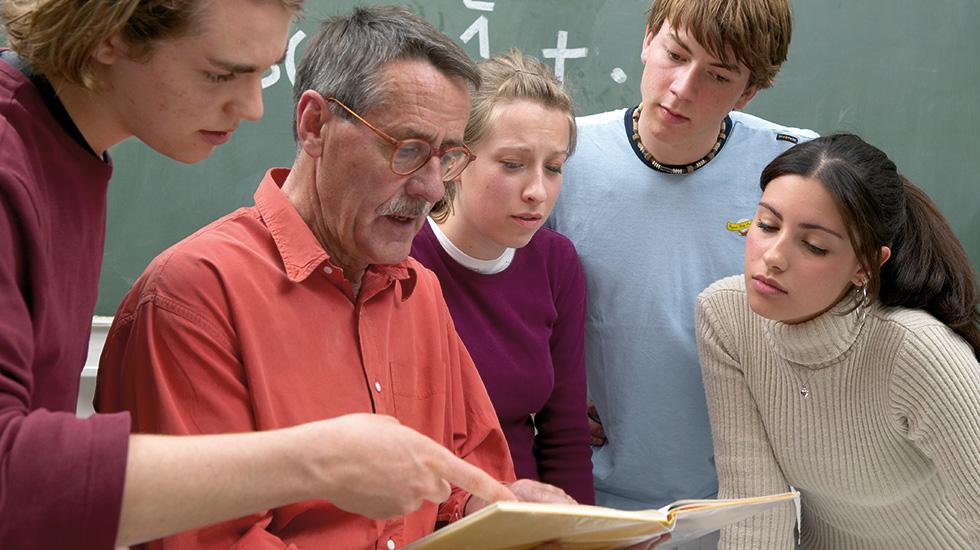 Gruppe Schueler bei Lehrer im Klassenzimmer
