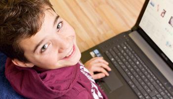 Freundlicher Junge –  Kind mit Notebook – Laptop auf dem Schoß
